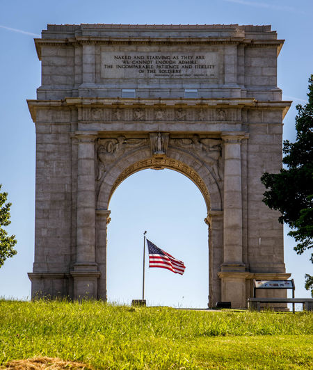 "Valley Forge National Memorial Archway.- The Memorial Arch is dedicated ""to the officers and private soldiers of the Continental Army December 19, 1777 June 19, 1778"". The Arch is situated at the top of a hill at the intersection of Gulph Road and Outer Line Drive in Valley Forge National Historical Park. The Arch was erected in 1910 by an act of the 61st Congress. Initially, in 1908, it was proposed to erect two memorial arches in the park, but the bill was amended to create a single arch to save money. It is modeled on the Arch of Titus in Rome. The architect in charge of the arch was Paul Philippe Cret, a professor at the University of Pennsylvania. The arch was criticized by the Philadelphia Record who observed that arches are typically urban structures and questioned its location in a rural setting. The 60-foot high arch was dedicated on June 19, 1917 in a ceremony attended by a number of U.S. Congressmen. Paul Cret did not attend as he was then en route to France where he served as an interpreter for the U.S. Army Architectural Column Architecture Built Structure Cloud Culture Day EyeEm Best Shots Flag Grass Grassy Green Color Lawn Low Angle View Memorial Archway Monument No People Outdoors Pole Road Sign Sky Soldier This Week On Eyeem Travel Destinations Tree Valley Forge National Park"