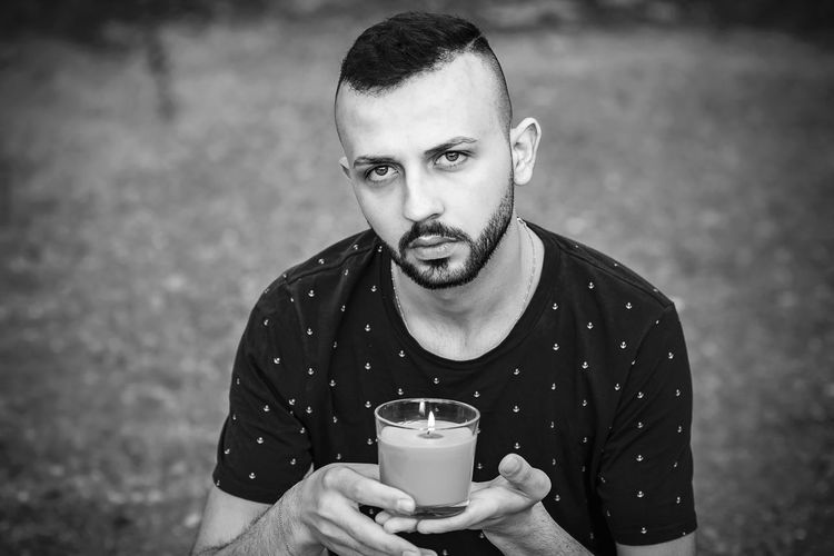 Portrait of young man drinking glasses outdoors
