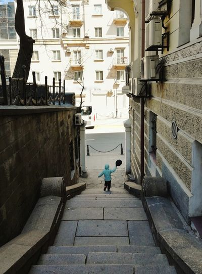 Rear view of girl walking on steps amidst buildings in city