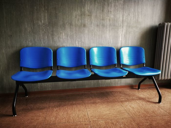 Empty blue chairs against wall
