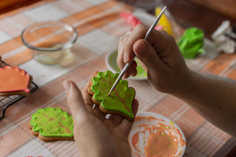 Cropped hands of woman preparing cookies at table