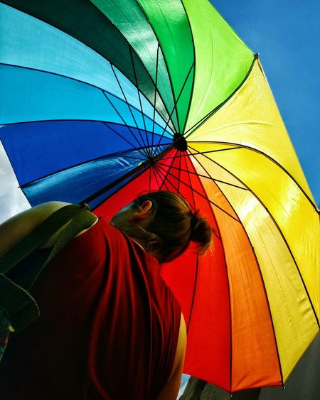 Low angle rear view of woman under colorful umbrella during sunny day