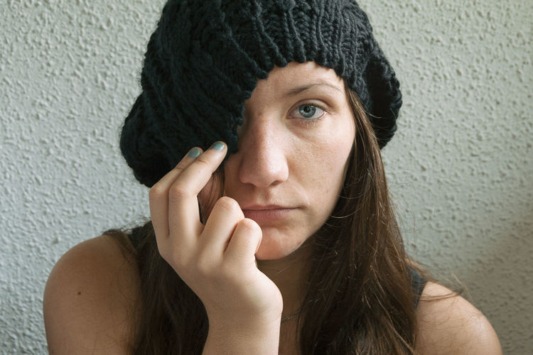 Young woman wearing knit hat against wall at home