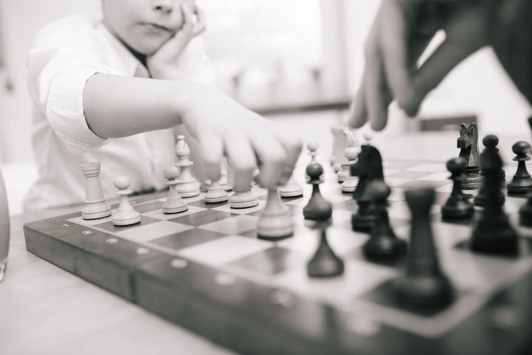 Midsection of boy playing chess