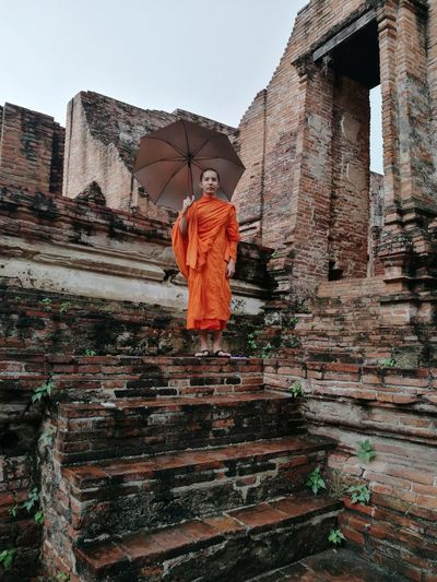 Low angle view of portrait monk standing with umbrella in temple