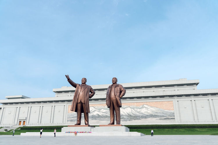 The Grand Monument on Mansu Hill (Mansudae) is a complex of monuments in Pyongyang, North Korea. The central part of the monument are two 22 meters high statues of North Korean leaders Kim Il-sung and Kim Jong-il, made of bronze. Behind the statues is a wall of the Korean Revolution Museum building, displaying a mosaic mural showing a scene from Mount Paektu, considered to be the sacred mountain of revolution. Next to the statues, leading away from the building, there are two monuments showing many different soldiers, workers, farmers, and so on; Anti-Japanese Revolutionary Struggle and Socialist Revolution. Communist Monument DPRK DPRKorea Juche Kim Il Sung Kim Jong Il Korea Korean North Korea Socialist Realism Built Structure Day Sky Socialist Been There.