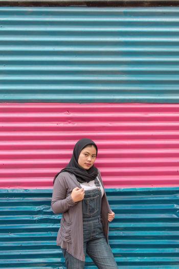 Portrait of girl standing against metal in city
