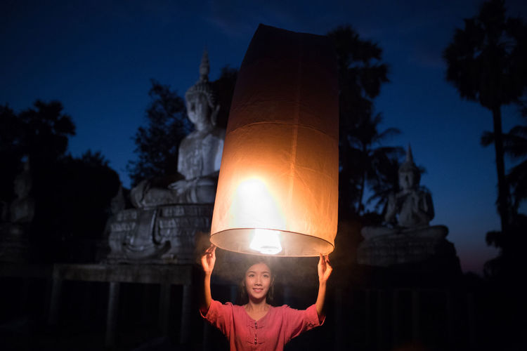 Young Woman Holding Illuminated Lantern While Standing Against Buddhist Temple At Night