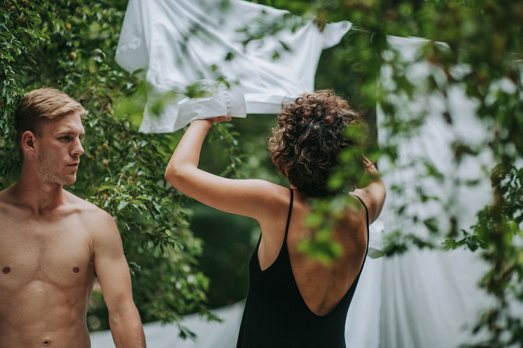 Rear view of shirtless man with woman standing by plants