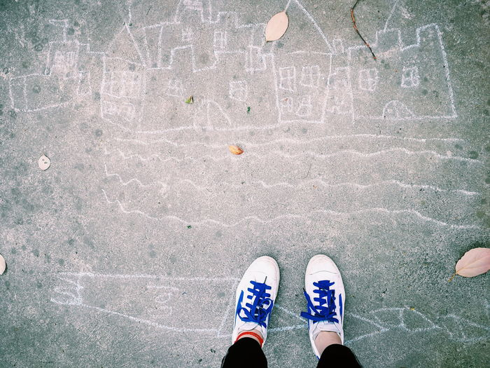 Low section of person standing by chalk drawing on footpath