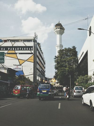 A tower in the distance Cars Small Buses Tower White Tower Muslim Place Of Worship Street Street Photography Car Incidental People Cloud - Sky Day Travel Destinations City Outdoors Architecture Sky Tree People