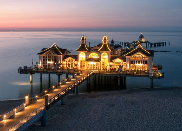 Illuminated pier by sea against sky at sunset