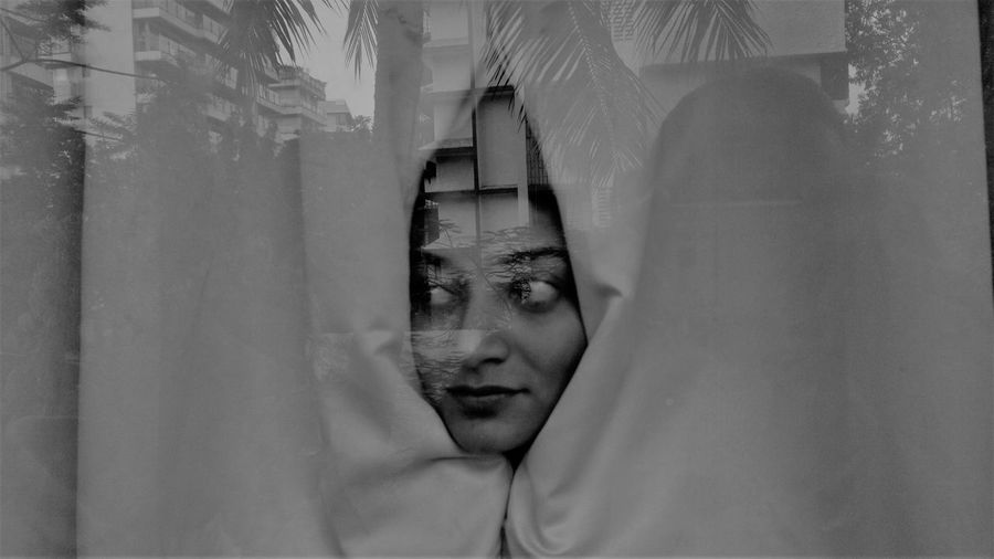Close-up of woman wrapped in curtain
