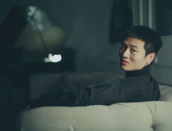 Portrait of young man sitting on sofa at home