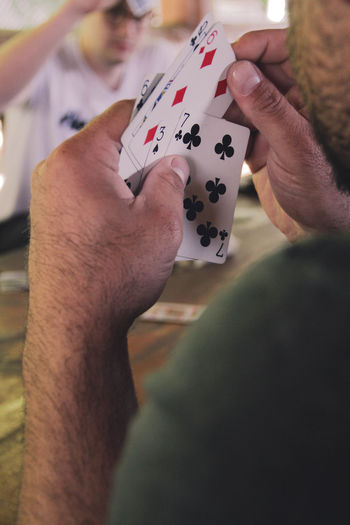 Cropped image of man playing cards at table