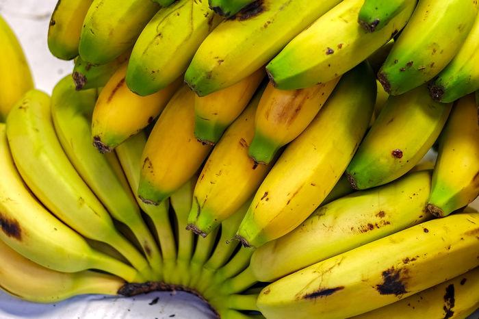 a bunch of bananas at the market Banana Fresh Produce Market Banana Banana Peel Banana Tree Bananas Bunch Of Fruits Close-up Day Food Food And Drink Freshness Fruit Fruits Green Color Healthy Eating Indoors  No People Yellow