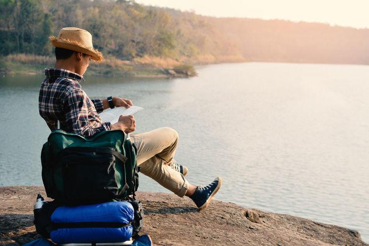 Young Man Reading At Lakeshore