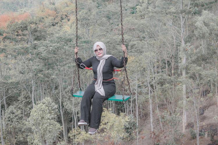 Full length of woman sitting on swing