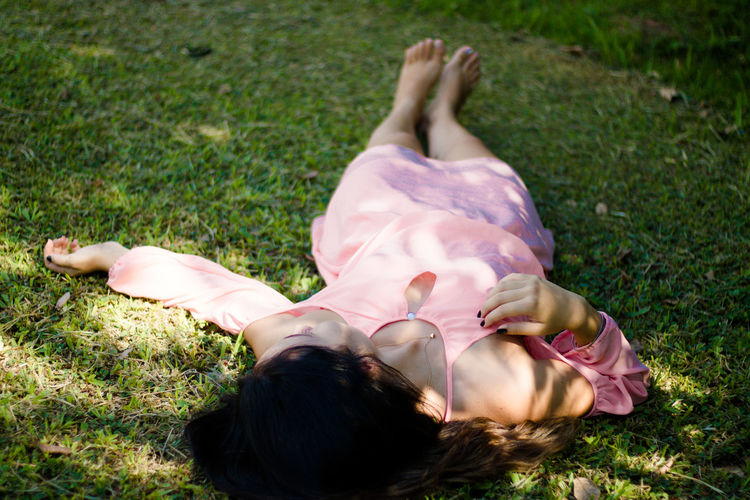 barefoot Child Day Females Field Girls Grass Hairstyle High Angle View Human Arm Land Leisure Activity Lifestyles Lying Down Lying On Back Nature One Person Outdoors Plant Real People Relaxation Women