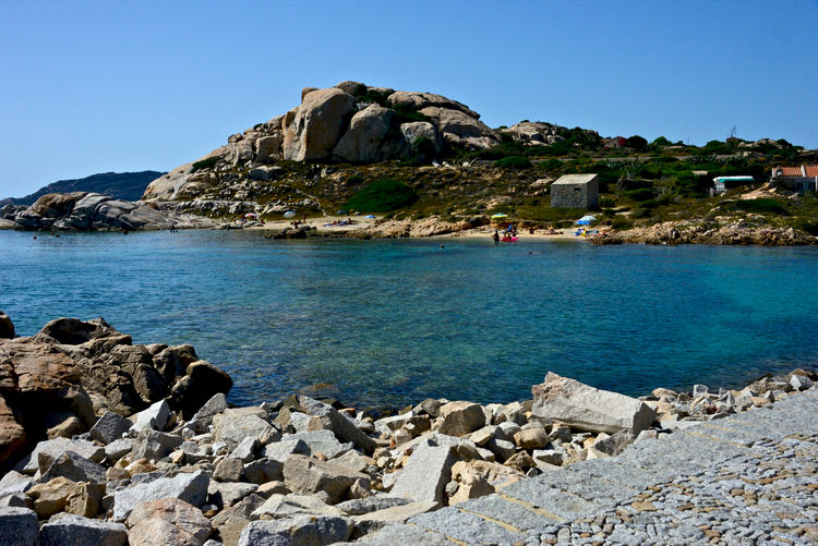 Scenic view of sea and rocks against clear blue sky