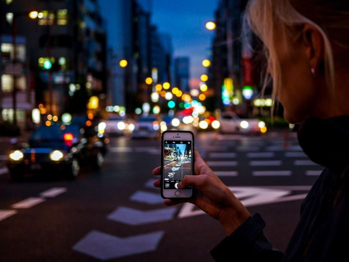 Midsection of woman photographing illuminated smart phone on street at night