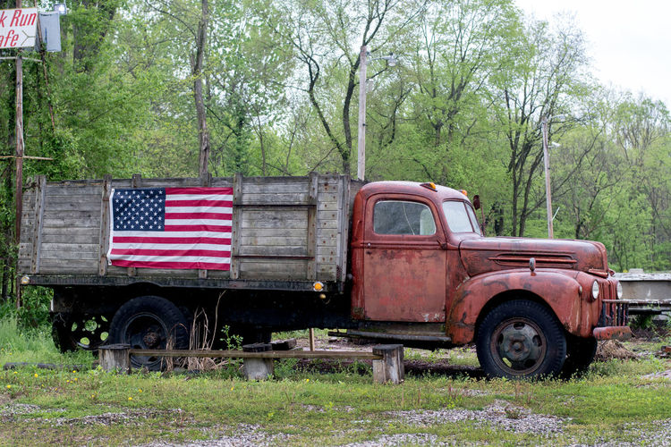 A vintage truck wears an American flag on it's side, as it sits parked along the road in rural Indiana USA Old Truck American Vintage Broken Grass Rundown Red Flag Vehicle Transportation White Patriotism Independence Beautiful Nation Day State Image Concept Background Country Classic Design National Government Show Art America Patriotic Style Freedom Graphic Stripes States Symbol Glory Banner Blue Rusty Antique USA Wooden Box Bed Sturdy Stars And Stripes Americana Mode Of Transportation Motor Vehicle Stationary Outdoors