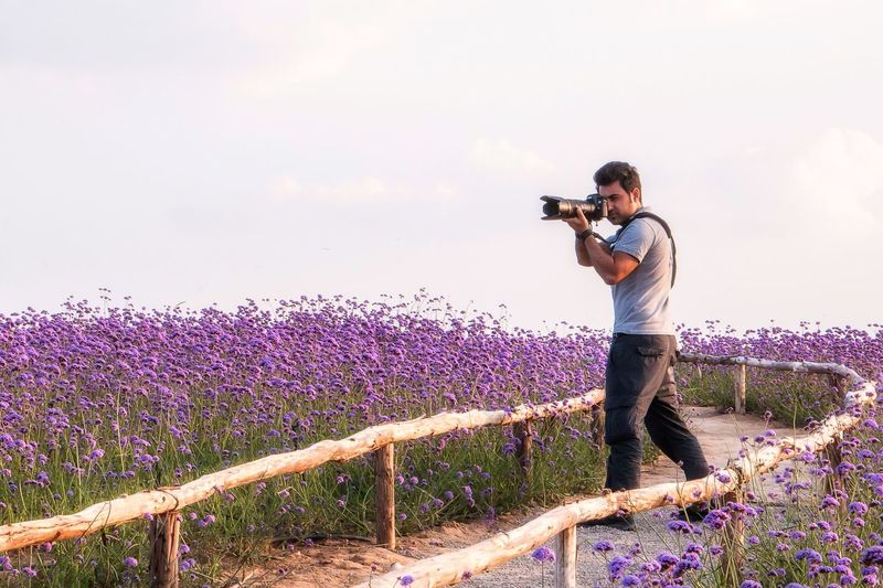 Full length of man photographing on field against sky