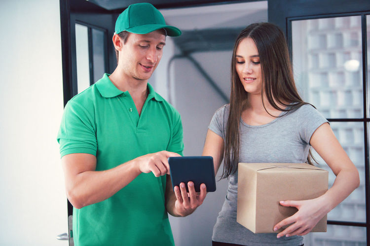 Young couple holding smart phone while standing on laptop