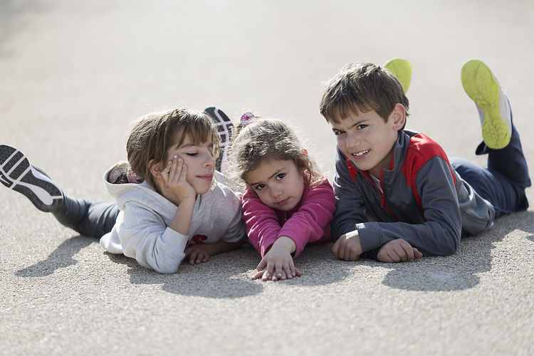 Three children lying on the floor one on top of the other. Horizontal shot with natural light Children Children's Portraits Spanish Tree Children Boys Caucasian Ethnicity Child Childhood Day Looking At Camera Looking At The Camera Outdoors People person Portrait Real People Smiling Sunlight Togetherness