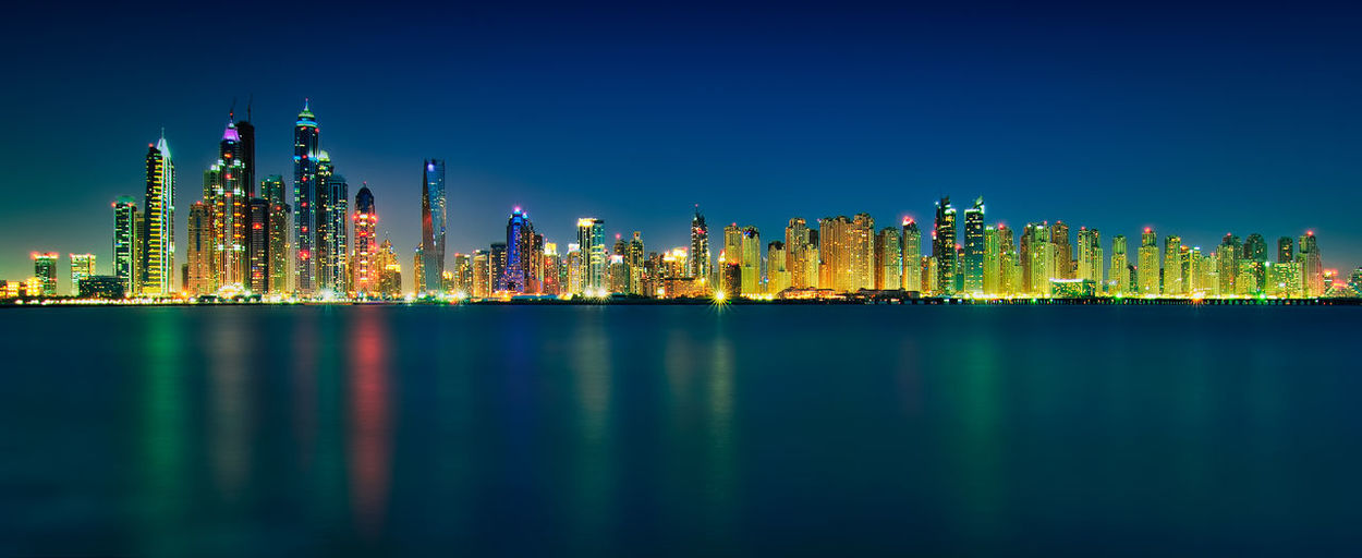 Panoramic view of illuminated buildings and sea against clear sky at night