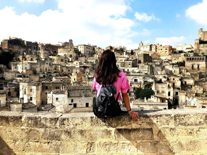Rear View Of Young Woman Looking At Townscape While Sitting On Retaining Wall Against Sky