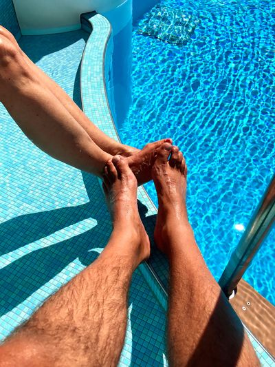 Low Section Of Couple By Swimming Pool During Sunny Day