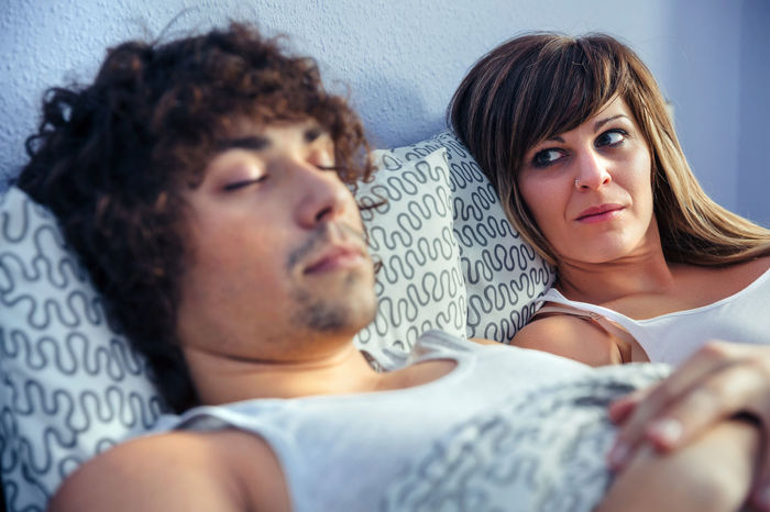 Frustrated and angry woman looking to young man sleeping in bed. Couple relationship and problems concept. Angry At Home Bed Couple Horizontal Lifestyle Love Man Relationship Romantic Unhappy Woman Bedroom Caucasian Female Intimacy Male Problem Quarrel Real People Relax Resting Togetherness Two People Young Adult