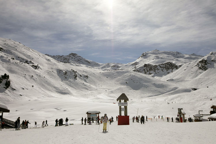 People On Snow Covered Mountain Against Sky