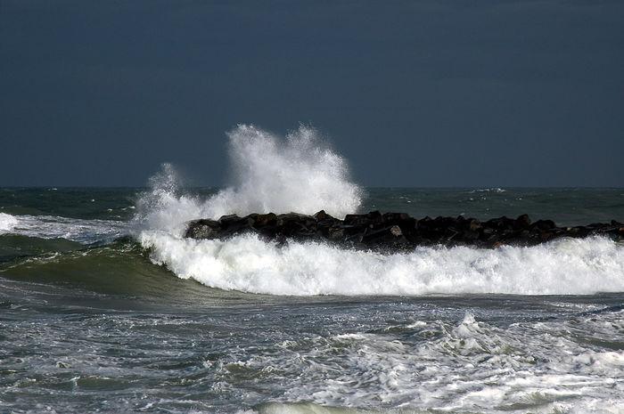 Waves hit the groynes on a storm beaten coast in Denmark Crash Dark Sky Denmark Roar Storm Swell Weather Weathered Beach Black Sky Ground Swell Groyne Roaring, Wave Sea, Seaw Seaway Splashing Spray Storm Cloud Structure Wave Breaker Wind