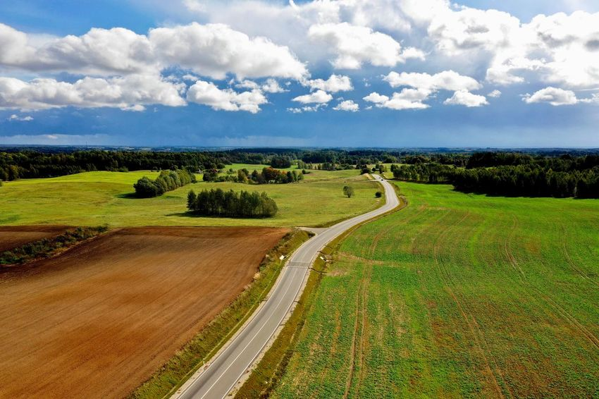 A road Plant Cloud - Sky Sky Beauty In Nature Landscape Environment Scenics - Nature Tranquil Scene Tranquility Growth Field Tree Day Nature Land Green Color Rural Scene Outdoors No People Agriculture