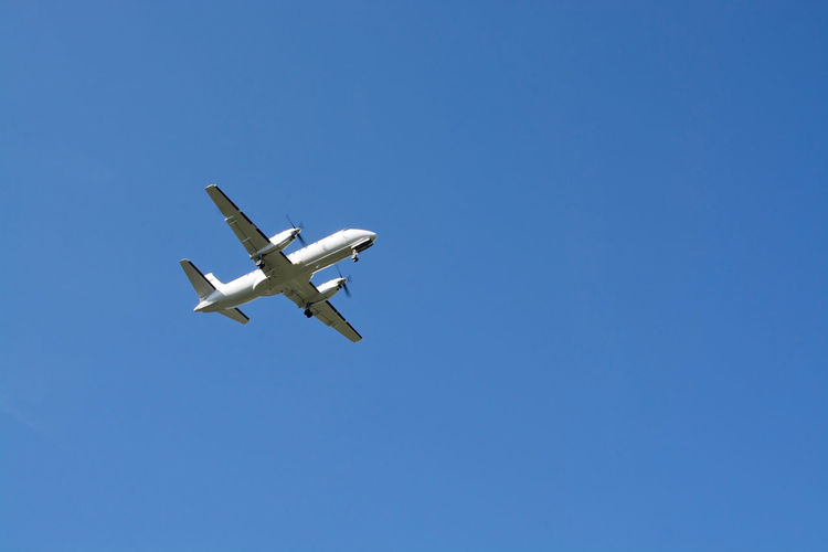 Low angle view of airplane flying against clear blue sky