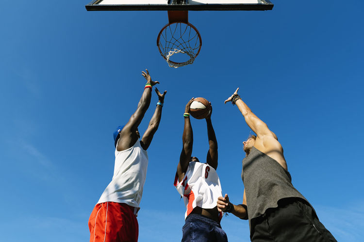 Low angle view of basketball hoop and men against blue sky