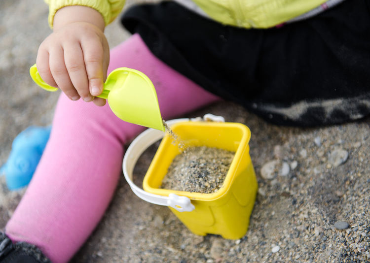 Child playing with plastic shovel and basket Baby Pebble Beach Sandbox Sitting Activity Baby Girl Beach Child Childhood Close Up Close-up Human Body Part Human Hand Little Girl One Person Outdoors Outside Plastic Toys Play Playing Real People Sand Sand Pail And Shovel Sandpit Unrecognizable Person