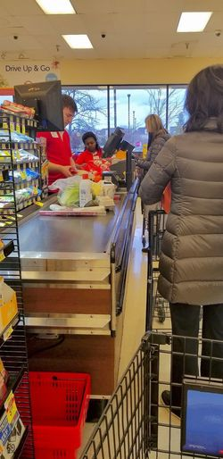 Housewives in winter coats stand in a checkout lane at a grocery store as their groceries are checked out by the cashier and clerk Wintertime Coats Store Business Women Indoors  Standing Group Of People Real People Domestic Activity Customer Service Clerks Cashier  Working Housewives Shopping Cart Shopping Groceries