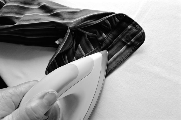 Close-Up Of Person Ironing Shirt