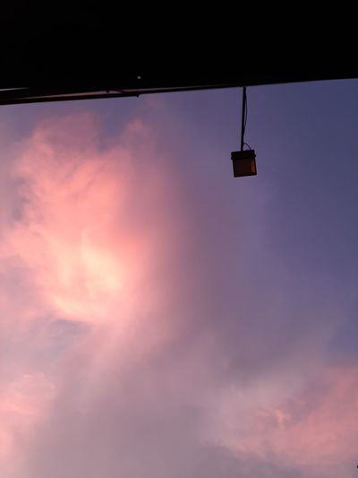 Low angle view of silhouette light against sky at sunset
