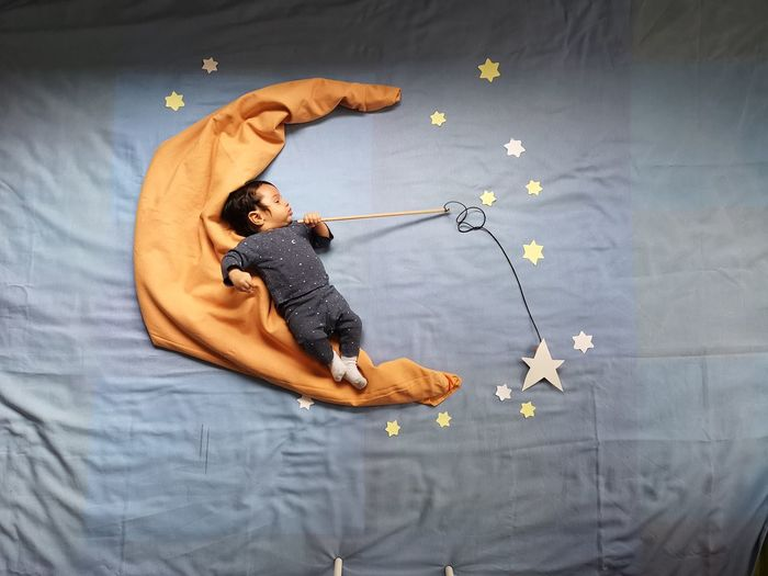 High angle view of baby boy with star decorations sleeping on bed at home