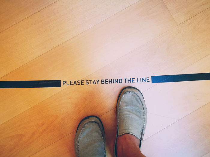 Please Stay Behind The Line LINE Please Stay Behind The Line Floor High Angle View Human Body Part Human Leg Indoors  Low Section Men Personal Perspective Real People Shoe Standing Text