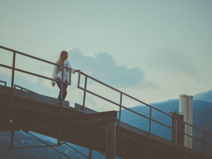 Low angle view of woman standing on railing against sky