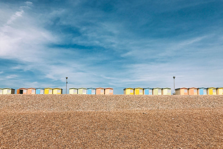 Beach huts on shore against sky