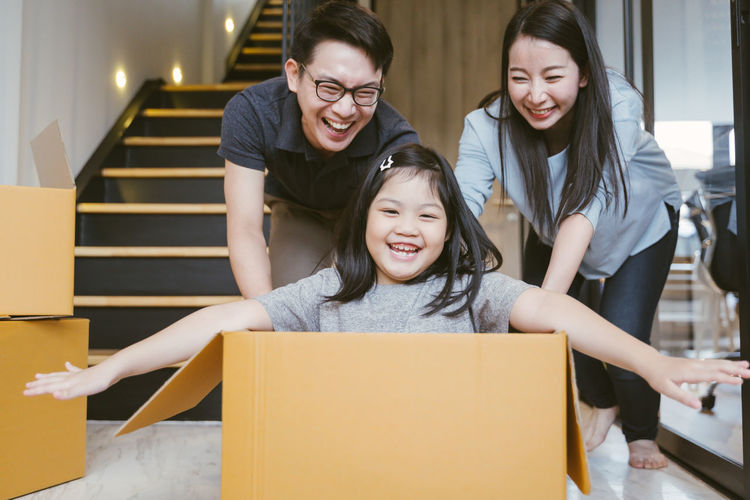 Portrait of happy Asian family moving to new house with cardboard boxes. Asian  Family Happiness Happy Happy People Family Time Home House Daughter Parent Father Mother Dad Mom Love Lifestyles Living Room ASIA Japanese  Korean Thai Taiwan Smiling Smile Fun Portrait Girls Moving New Home Playing Estate Move Box