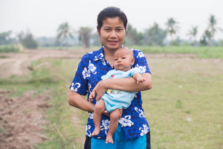 Portrait of woman carrying toddler son while standing on field