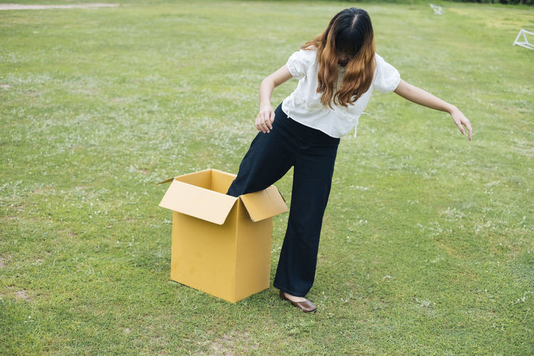 Full length of woman coming out of box on grass