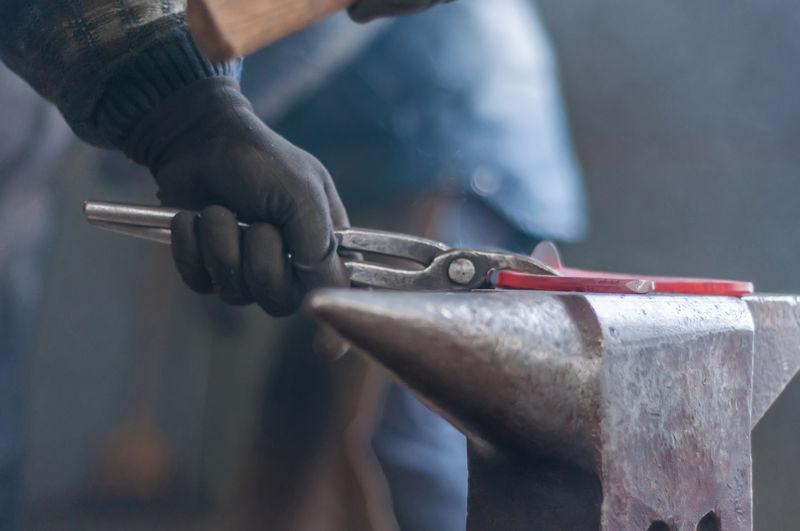 Cropped image of blacksmith making horseshoe in industry